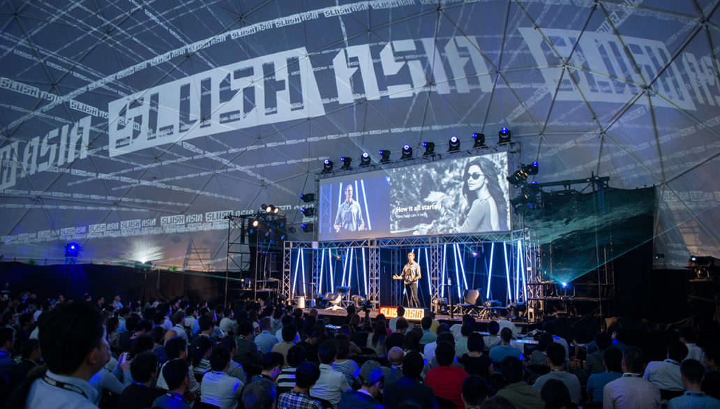 A photo from Slush Japan event shows a large crowd of people gathered by a stage where someone is presenting.