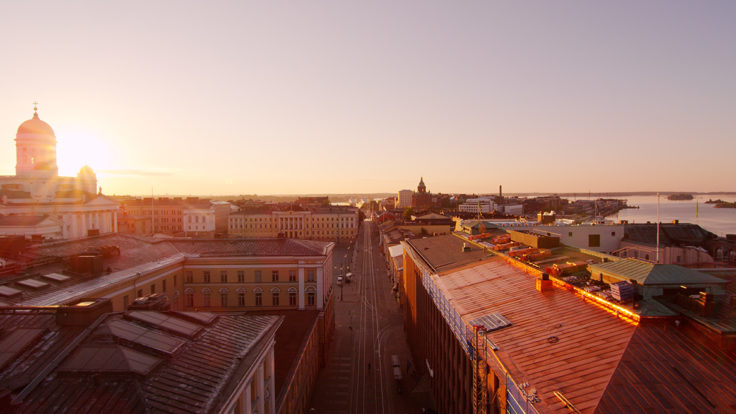 A silhouette of Helsinki rooftops in sunset, Helsinki cathedral in the background.