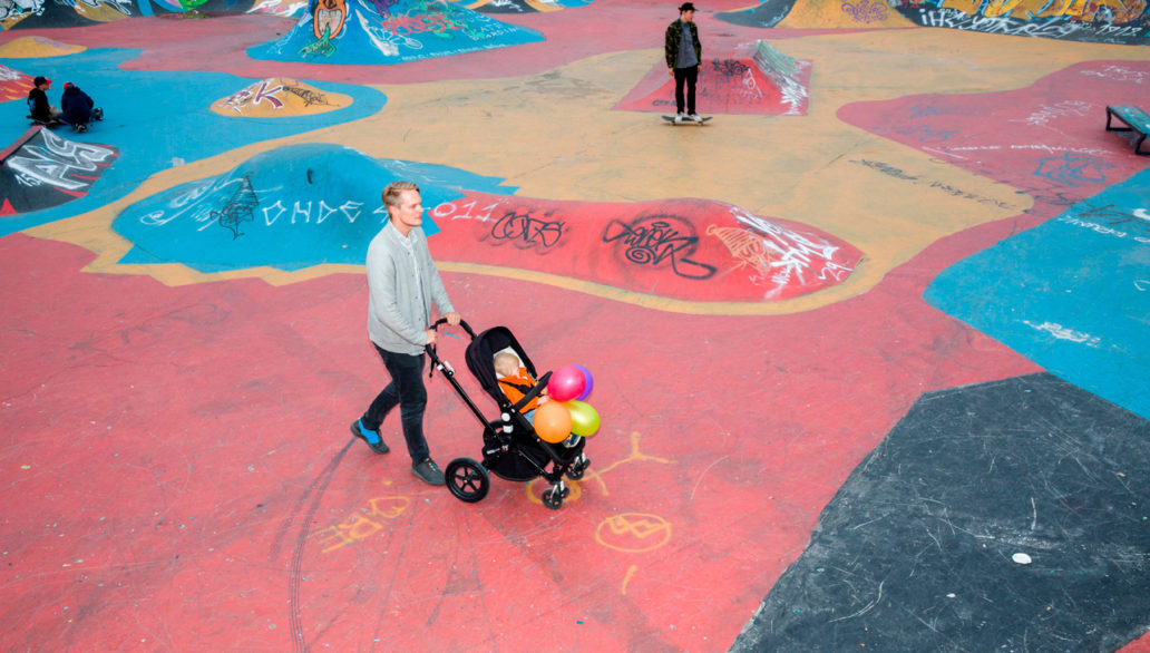 A man pushing a stroller at a colourful skate park with skaters in the background.