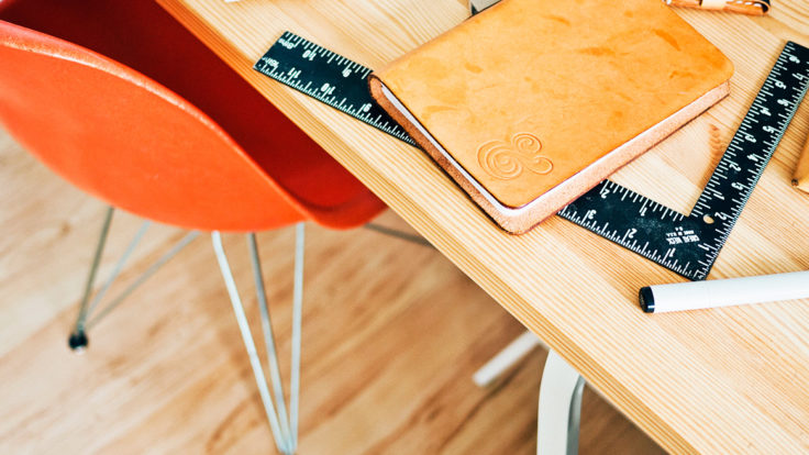 A notebook, ruler and pen on a wooden desk.
