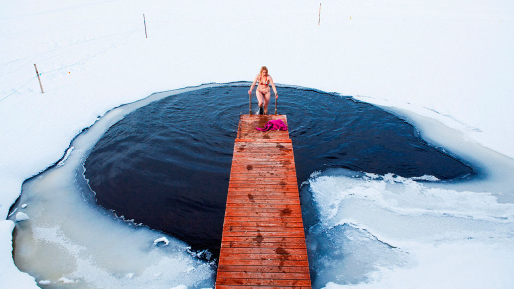 A woman in bikinis climbing on a pier after a swim in a hole in the ice.