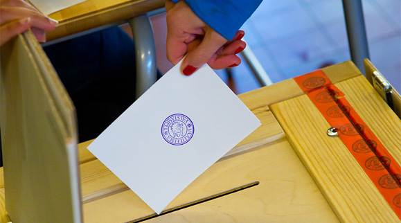 A person putting their voting ballot in a ballot box.