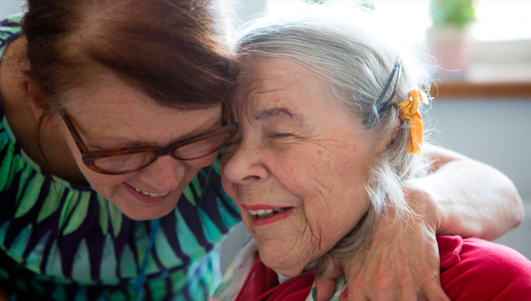 Two elderly women hugging.